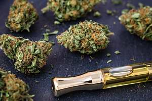 Cannabis cartridge on table with flower
