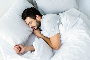 a person sleeping after figuring out what strain of weed helps them sleep better
