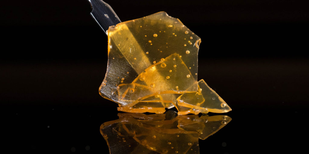 close up of cannabis resin on a black background using a stick