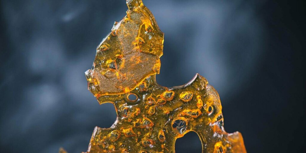 abstract detail of cannabis oil concentrate aka shatter with smoke over dark background