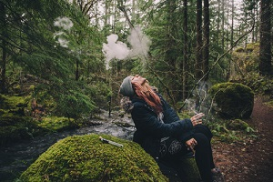 blonde woman smoking cannabis while hiking in the woods getting Weed Hangover