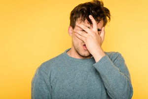 man frustrated man covering his face because of a Weed Hangover