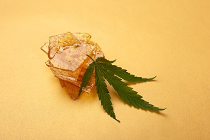 pieces of yellow cannabis wax and green leaf
