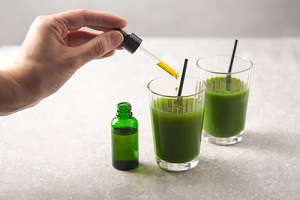 cbd oil dropper bottle and cannabis infused green health drink