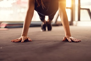 woman hand doing push ups exercise in a gym